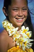 Young island girl, age 9-10, wearing a yellow plumeria lei and hula costume in Hawaii