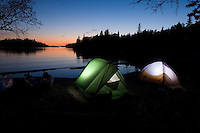A pair of tents glow at dusk during a sea kayaking trip at Chalfant Cove in Lake Superior Provincial Park near Wawa Ontario Canada.
