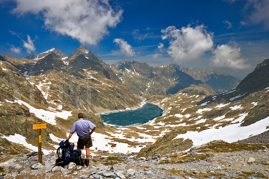 Parc National du Mercantour.   Walker admires the view of the Lac du Basto surrounded by high peaks, from the  Baisse de Valmasque, 2549m, Alpes-Maritimes, Provence, France.  Model released.