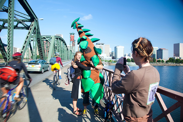The Hawthorne Bridge spans the Willamette River in Portland, Oregon joining Hawthorne Boulevard and Madison Street.  It is the oldest vertical lift bridge in operation in the United States.  It is also the busiest bicycle and transit bridge in Oregon with over 4800 cyclists and 750 TriMet buses daily.  Pictured here is Friends of Trees volunteer Greg Tudor who dresses up in a tree costume to wave to bicycle and car commuters to raise awareness for their organization which plants and cares for city trees and urban natural areas.