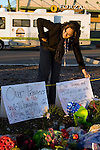 Monet Thompson straightens a sign she put near a memorial of flowers, balloons, and wreaths for four slain police officers at the Forza Coffee Shop  in Lakewood, Washington, USA, on 2 December  2009. Four Lakewood officers were gunned down during a morning meeting at a local coffee shop on 29 November 2009. Jim Bryant Photo. ©2010. ALL RIGHTS RESERVED.