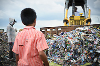 Taupik, 14, watching a bulldozer approach on the 'Trash mountain', Makassar, Sulawesi, Indonesia.  Many of the pickers follow the bulldozers as they move newly dumped waste, uncovering plastic and metal for recycling in the process.