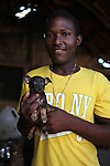 Cristian Gálvez Suárez, 18, from La Cerca, plays with his puppy. Barrick and Goldcorp's Pueblo Viejo open-pit gold mine threatens the cocoa-bean producing community of La Cerca. Cotuí, Sánchez Ramírez, Dominican Republic. April 2012.