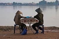 Elderly people overlooking the Mekong River towards Thailand in Vientiane