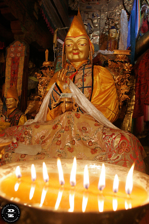 Yak butter candles illuminate a statue of one of the Dalai Lamas at the Main Assembly Hall at  Sera Monastery in Lhasa, Tibet.  Photograph by Douglas ZImmerman