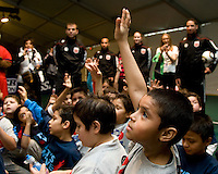 Local children wait to ask questions during a presentation on nutrition given by White House Chef Sam Kass during a US Soccer Foundation clinic held at City Center in Washington, DC.