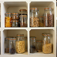 Storage jars of different sizes and contents are stacked in keeping holes on kitchen shelves