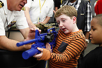 New York, USA. 22nd May, 2014. A boy check a simulate riffle during the Fleet Week at pier 92 in Manhattan, New York.  Kena Betancur/VIEWpress