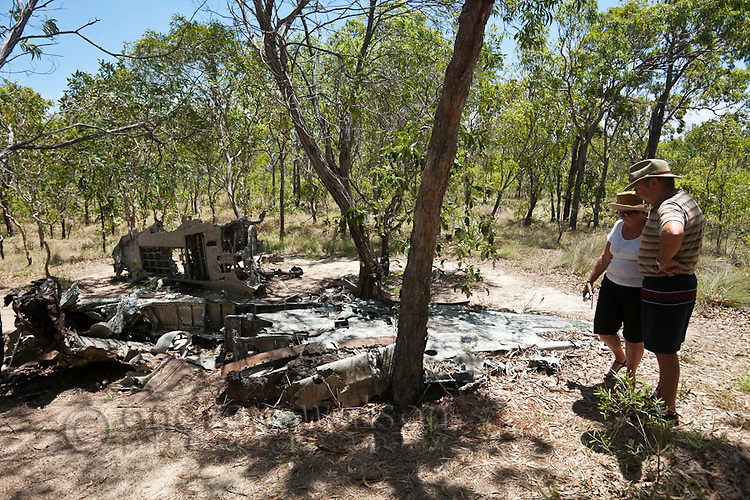 Tourists at the wreckage of a World War II aircraft on Horn Island.  The island was a strategic outpost during WWII and was bombed numerous times by the Japanese.  Horn Island, Torres Strait Islands, Queensland, Australia