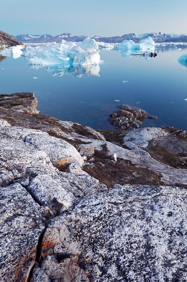 Icebergs and bedrock at dusk along Sermilik Fjord near settlement of Tiniteqilaq, East Greenland
