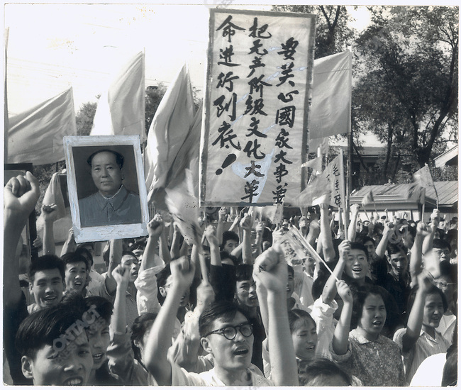 Li cropped and retouched this photograph of a rally in Harbin at the request of his editors at the Heilongjiang Daily. In the original, marchers' fists seem to strike Mao's portrait; Mao's picture is in a black frame - which implies that his is dead; and the sign bearing Mao's quotation is partially obstructed by a waving flag. Li removed the fists and black frame, and redesigned the hidden characters of the quotation.