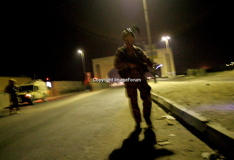 Members of the Royal Air Force Regiment 1 Squadron check the road-edge for IEDs (Improvised Explosive Devices) after they pass an Iraqi Police check-point at Basra Arches while carrying out a night patrol on the perimeter of Basra Airport Base in southern Iraq, in the early hours of 12 October 2005, ahead of the constitutional referendum on 15 October. The RAF Regiment is tasked with protecting airbases and other RAF assets around the world. AFP PHOTO / JOHN D MCHUGH