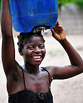 "A young woman carries water in Chidyamanga, a village in southern Malawi that has been hard hit by drought in recent years, leading to chronic food insecurity, especially during the ""hunger season,"" when farmers are waiting for the harvest."