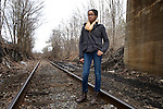 A teenage African American standing on the railroad tracks
