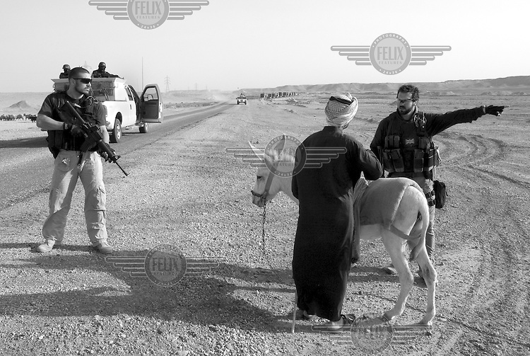 Private security operator Karl Moore (right) speaks with a local shepherd on the notoriously dangerous road between the military outpost Camp Wolf  and Al Asad air base in north western Iraq on November 2, 2006. His colleague Mick Holgate stands by. In the background a convoy escorted by the British company ArmorGroup has been stopped by improvised explosive devices. The coalition forces and civilian administration in Iraq depend heavily on the controversial presence of thousands of private security personnel in their reconstruction efforts and military operations.