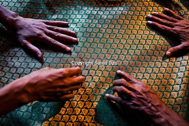 weavers cut small threads out of the final silk piece in their workspace in Gazi Sadullahpura Bade Bazaar in Varanasi in Uttar Pradesh, India. Photograph: Sanjit Das/Panos