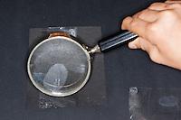 Fingerabdruck, Fingerabdrücke nehmen, 5. Schritt:  das durchsichtiges Klebeband wird mit dem durch Puder sichtbar gemachten Fingerabdruck auf eine schwarze Pappe geklebt, der Fingerabdruck kann nun gesammelt, mit einer Lupe untersucht und vergleichen werden