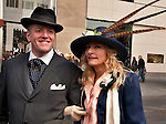 A couple wearing their Sunday best clothes and hats, with the woman wearing a hat with three long feathers, in the Easter Parade in New York City