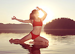 Young woman practicing Hatha yoga on a floating platform in water on the lake in early morning sun light. Yoga Pigeon posture variation, Kapotasana. Muskoka, Ontario, Canada.