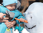 Little boy grabbing snowman's carrot nose
