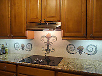 Custom stone hand chopped tumbled scroll-acanthus mosaic kitchen backsplash.