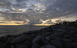 Sun setting through the clouds over La Gomera, Canary Islands. Taken from Bahia del Duque beach, Tenerife, Canary Islands.
