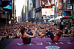 People attend a morning yoga practice on the summer solstice in New York's Times Square  in New York June 20, 2012.  Photo by Kena Betancur / VIEWpress..