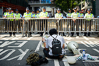 HONG KONG, HONG KONG SAR, CHINA - SEPTEMBER 30: A protestor sits and reads a newspaper as part of a pro-democracy sit-in known as 'Occupy Central', facing police officers on Arsenal Road, in front of police headquarters, in Admirality, Hong Kong, on September 30, 2014. The Occupy Central civil disobedience movement began in response to China's decision to allow only Beijing-vetted candidates to stand in the city's 2017 election for the top civil position of chief executive. (Photo by Lucas Schifres/Getty Images)