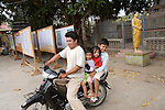 Bunroeun takes a ride on a scooter motorbike with his uncle and 2 cousins to visit the local Buddhist pagoda..A Khmer boy learns to play classical violin at the college of Beaux Arts, at the edge of Cambodia's capital, Phnom Penh. He is an orphan and comes from a poor family. His parents died long ago, from AIDS related diseases. He lives with his grandmother and his uncle, and their family. He lives on the top floor of an apartment block, where his family run a textile business, sewing together clothes and ornamental flags from around the world. A dozen young women work in this textile business, and the boy's home space is actually amidst this small factory environment which he shares with them. They eat, work and play together like an extended family or community. Phnom Penh, Cambodia
