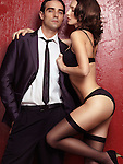 Sexy couple portrait of young man wearing a business suit and a seductive young woman in black lingerie and stockings on red background
