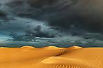 Sahara sand dunes with stormy, cloudy sky at Erg Lihoudi, M'hamid, Morocco.