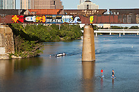 Sunny summer day welcomes rowing crew and SUP paddle boarders pass underneath the Union Pacific Railroad Graffiti Bridge as a train passes over Lady Bird Lake in downtown Austin, Texas.