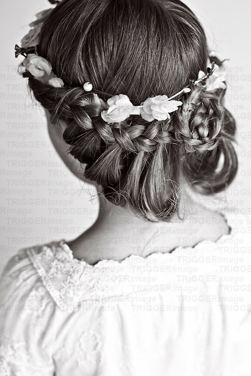 Female youth with hair in plait wearing white dress looking away from camera
