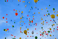 Brightly colored balloons floating across a blue sky.