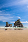 Blue skies and golden sand at Archway Islands, Wharariki Beach, New Zealand.