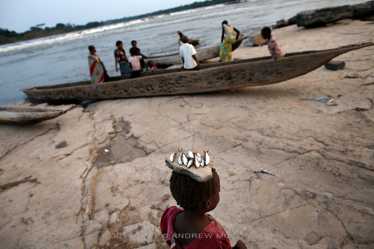 A girl carries freshly caught fish on her head, at Wagenia Falls, DR Congo.