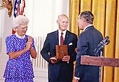George F. Kennan, Diplomat, Political Scientist, and Historian, center, is awarded the Presidential Medal of Freedom, the highest civilian award of the United States, by US President George H.W. Bush, right, and first lady Barbara Bush, left, in a ceremony in the East Room of the White House in Washington, DC on July 6, 1989.  Kennan was known as an advocate of a policy of containment of the USSR  and lectured and wrote about the history of relations between the Soviet Union and the United States.<br /> Credit: Ron Sachs / CNP