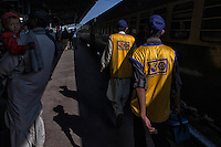 Pakistani Health workers walk and administer polio drops to children before boarding to the train departing from Karachi city to other provinces at the railway station in Karachi, Pakistan on Jan. 08, 2014