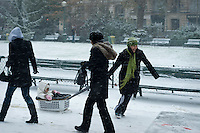 Woman using a washing basket as a sledge to pull her child through the snow in a Paris park.