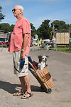 Elderly man with pet dog in shopping basket. Priddy Sheep Fair Somerset Uk 2009.