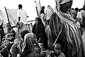 Somalian refugees wait while Kenyan officials are seen registering them to a database at a government registration point in the IFO Camp of the Dadaab refugee camp in northeastern Kenya. Hundreds of thousands of refugees are fleeing lands in Somalia due to severe drought and arriving in what has become the world's largest refugee camp. Photo: Sanjit Das/Panos