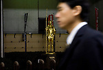 A man walks past a golden statue of the mythical Kappa creature, which has become an emblem of the Kappabashi district of Tokyo, Japan on Nov. 10 2010. Often called Tokyo's Kitchen Town, stores in Kappabashi still mainly caters to professionals in the catering industry, though is becoming increasingly popular with foreigners hunting for unique souvenirs..Photographer: Robert Gilhooly