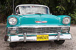 Finca La Vigia, San Francisco de Paula, Cuba; a teal blue and white classic 1956 Chevrolet car in the parking lot of the Hemingway Museum