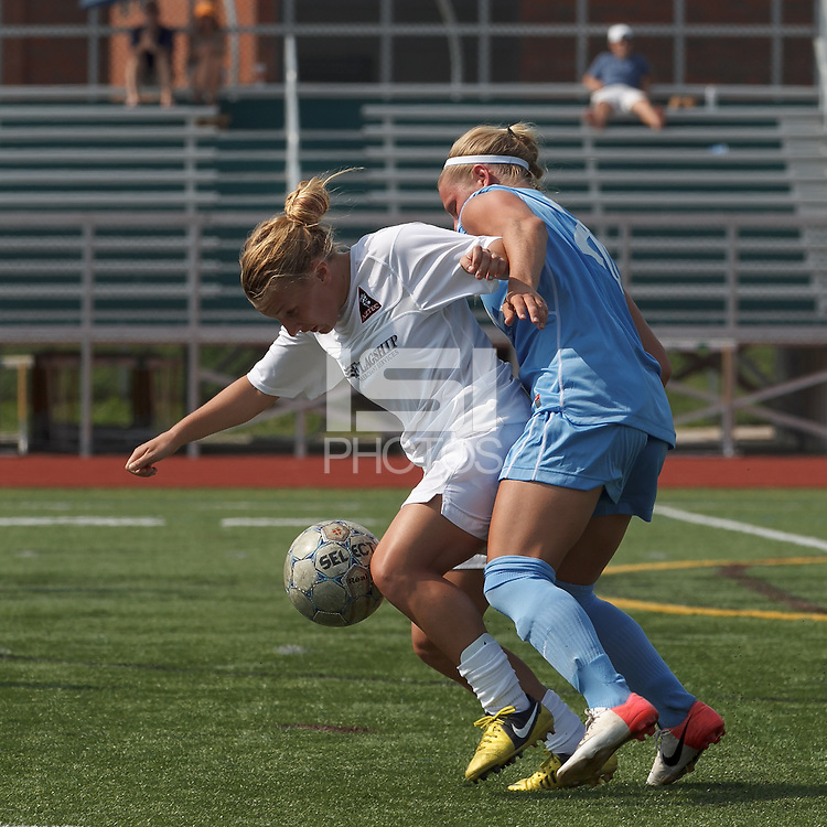 Boston Aztec midfielder Riley Houle (22) controls the ball as Seacoast United Mariners defender Ida Bjerklund (20) closely pressures. In a Women's Premier Soccer League (WPSL) match, Boston Aztec (white) defeated Seacoast United Mariners (blue), 2-1, at North Reading High School Stadium on Arthur J. Kenney Athletic Field on on June 23, 2013. Due to injuries through the season, Seacoast United Mariners could only field 10 players.