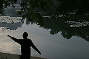 A man goes through his Tai Chi exercise routine in Green Lake Park, early in the morning. Kunming, China