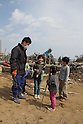 March 29, 2011, Minamisanriku, Miyagi, Japan - More than two weeks after the tsunami the rural area between Kesennuma and Minamisanriku lies in ruin. Koyo Okoshi (9), Saya Okoshi (6), Yu Kono (8) and Tatsuya Kono (10) help Mr. Okoshi search for bottles of sake from his destroyed business. (Photo by Wesley Cheek/AFLO) [3682].