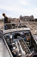 A Moudjahidin in what remain of the King Daimler DK400 car, in the courtyard of the Afghan Kabul National museum in Spring 1995. On the back left, the burn and loot museum and on the right, the destroy Darulaman Palace.