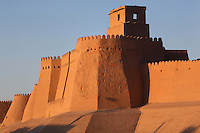 Low angle view of a bastion on the walls of the old city, Khiva, Uzbekistan, pictured on July 6, 2010, at sunrise. Khiva's old city, Ichan Kala, is surrounded by 2.2 kilometres of crenellated and bastioned city walls. Some sections may be 5th century, but the strongest sections were built 1686-88 by Arang Khan. Khiva, ancient and remote, is the most intact Silk Road city. Ichan Kala, its old town, was the first site in Uzbekistan to become a World Heritage Site(1991). Picture by Manuel Cohen.