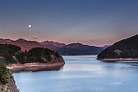 Full moon at sunset over the Snake River Range and Palisades Reservoir in Swan Valley Idaho