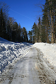 Narrow gravel  country road in winter, vertical shot